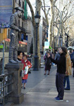 A girl talking to a statue at La Rambla - a street that is very crowded during weekends.