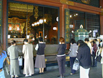 Inside the Sensoji Temple, people are throwing coins in a big well. The dropping coins make a lot of noise.