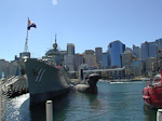 A warship and a submarine made into a museum in Darling Harbour. The Central Banking District in the background.