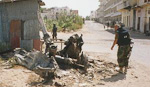 A Norwegian soldier takes a look at what is left of a US helicopter that was shot down over Central Mogadishu.