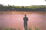 This is me in front of a river full of hippopotamuses. I guess they all got so scared of me that they dived when this picture was taken. If you look closely, you might see the eyes of at least two hippos behind me.